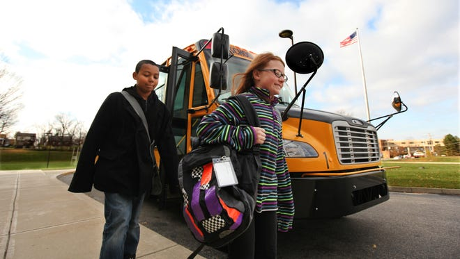Sixth-grader Jaythan Wright, 11, and fourth-grader Abby Ahrens, 9, at Dater Montessori in Cincinnati were among the first in a Cincinnati Public School program to be issued cards to swipe as they board and exit their school bus.