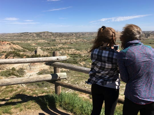 FILE--In this Wednesday, May 24, 2017, file photo, Jeanne Randall, right, and her daughter Zoe, of Shoreview, Minn., take photos at Painted Canyon in Theodore Roosevelt National Park in western North Dakota, near where a company wants to build an oil refinery about 3 miles from the park. A new study concludes visitors may be steering clear of some U.S. national parks or cutting their visits short because of pollution. (AP Photo/Blake Nicholson, file)
