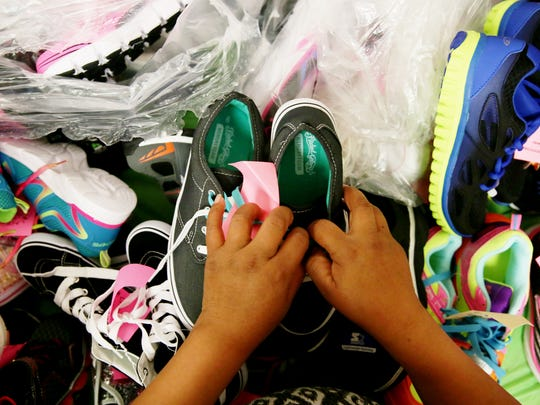 Parents look through shoes for their children during the Holiday Gift Shop at the Guadalupe Center in Immokalee on Wednesday, Dec. 14, 2016. Parents could pick out up to three gifts for free per child for Christmas.