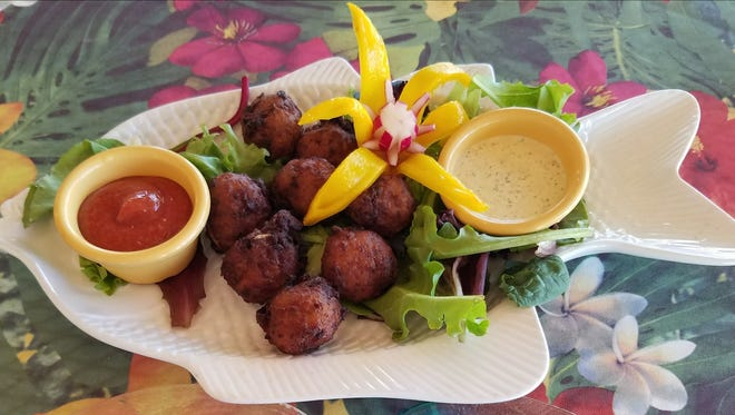 Flash Beach Grille's conch fritters have a homemade batter and are served on a fish shaped platter atop a bed of mixed greens with cocktail sauce and a remoulade. The platter was decorated with an edible tropical flower vegetable carving.