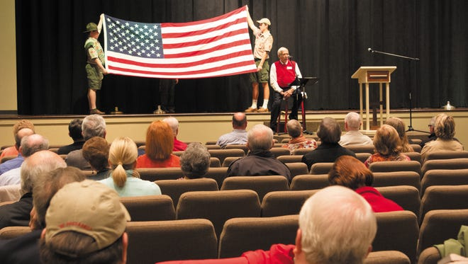 Scouts display an American flag as Tommy Buntin recites a poem Sunday at the Veterans Recognition Celebration at Northside United Methodist Church.