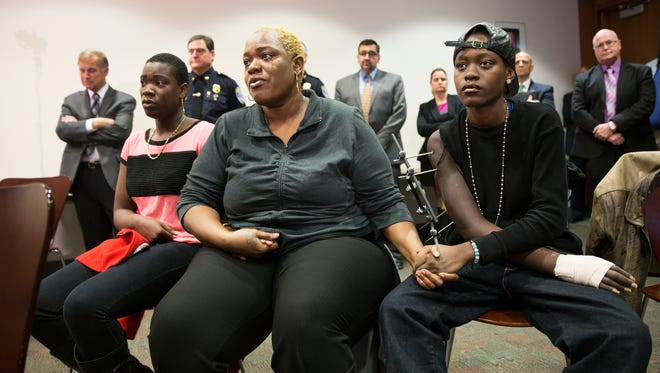 Shanell Anderson-Edwards holds hands with her mom, Delanese Anderson, and sister, Ebony Anderson, at a press conference in the Public Safety Building on Friday, November 13, 2015. Shanell Anderson-Edwards, 24, was shot on Aug. 16 on Genesee St. by the same gun that was used in the Boys & Girls Club shooting.