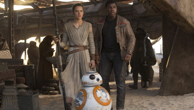 Rey (Daisy Ridley), Finn (John Boyega) and the droid BB-8 help launch the next chapter of Star Wars  on Thursday in Coachella Valley.