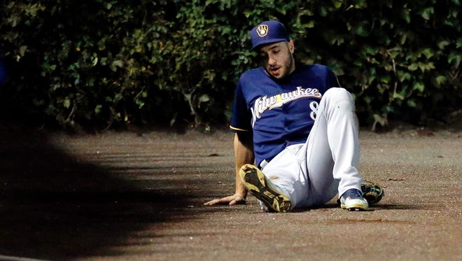 Ryan Braun of the Milwaukee Brewers sits on the ground after suffering an apparent injury after sliding into the wall while chasing a foul ball against the Chicago Cubs during the fourth inning in game two of a double header at Wrigley Field.
