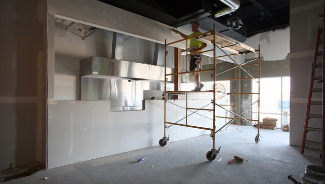 Ryan Hoyt of Newark Drywall works in the new BuckinBurger location Thursday on Log Pond Drive in Newark.