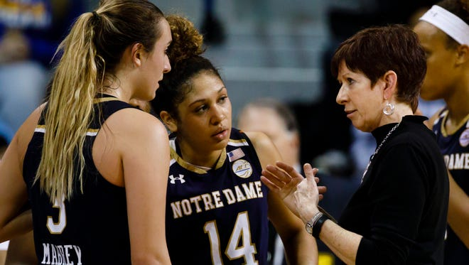 Notre Dame head coach Muffet McGraw, right, talks to guard Marina Mabrey (3) and guard Mychal Johnson (14) during a timeout against Toledo in the second half of an NCAA college basketball game, Sunday, Dec. 18, 2016 in Toledo, Ohio. (AP Photo/Rick Osentoski)