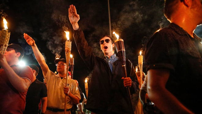 Multiple white nationalist groups march with torches through the University of Virginia campus in Charlottesville on Aug. 11, 2017.