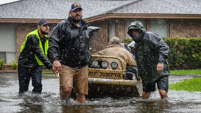 Volunteers and first responders help flood victims evacuate to shelters due to rising waters from Hurricane Harvey.