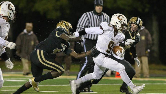 Central's Tor'Jon Evans worked to evade a tackle from Jasper's Malik Chatman, left, and Sam DeWitt in the first half of the Class 4A sectional game Friday evening at Jerry Brewer Alumni Stadium in Jasper. Central defeated Jasper 26-15.