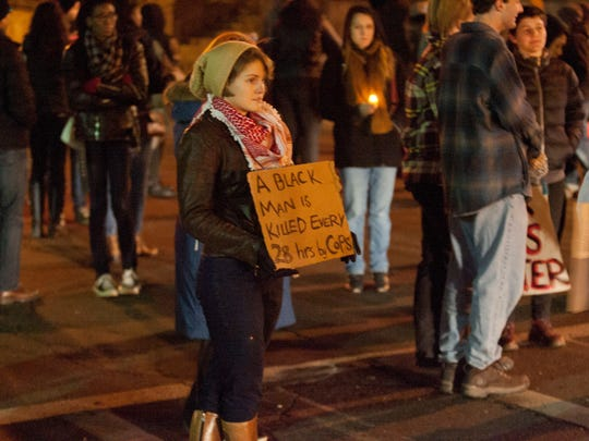 Protesters shut down portions of Tioga Street in Ithaca Tuesday night after a vigil to question the Ferguson, MIssouri grand jury decision to not charge police officer Darren Wilson in the shooting death of Michael Brown.