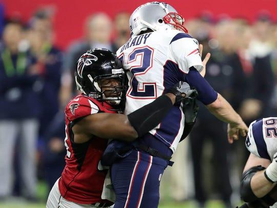 Patriots quarterback Tom Brady (12) is hit by Falcons