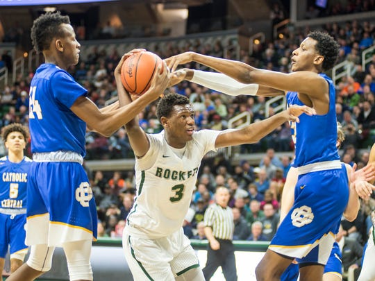 Grand Rapids Catholic Central's Mykel Bingham (24) and Marcus Bingham Jr. (right) steal the ball from New Haven's Ashton Sherrell during the MHSAA Class B basketball semifinals at the Breslin Center in East Lansing Friday, March 23.