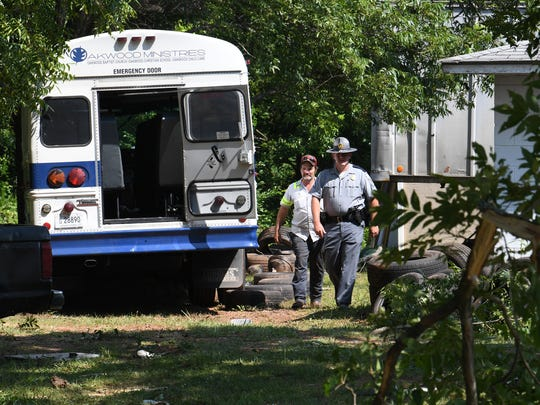 A State Trooper looks over the damage from an accident where a church bus from Oakwood Baptist Church crashed at 1611 Pearman Dairy Road in Anderson on Tuesday.