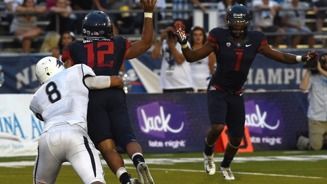 Arizona's Anu Solomon (12) gets off a forward pass to avoid getting tackled for a safety by Nevada's Ian Seau (8) during their football game at Mackay Stadium in Reno Saturday.