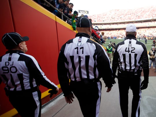 Referee Jeff Triplette (42) leads his crew onto the