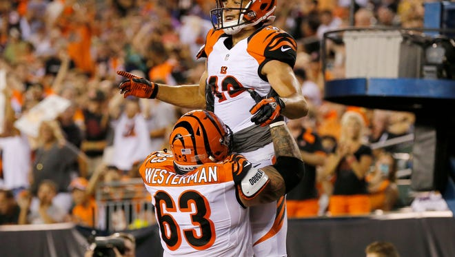 Cincinnati Bengals wide receiver Alex Erickson (12) and offensive guard Christian Westerman (63) celebrate Erickson's touchdown in the second quarter of the NFL pre-season game between the Cincinnati Bengals and the Minnesota Vikings at Paul Brown Stadium on Friday, Aug. 12, 2016. At halftime, the Vikings led 10-7.