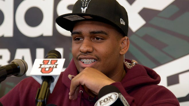 Long Beach Poly High defensive lineman Joseph Wicker announces his decision to attend Arizona State during a news conference on Wednesday.