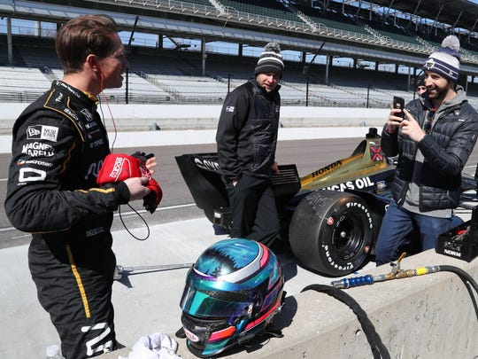 Aaron Telitz prepares to get into James Hinchcliffe's Indy car for his first as Hinchcliffe snaps his photo.