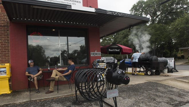 Chris Sowell, left, and Tim Whiteley relax with a soda outside City Grocery on 12th Avenue on Monday, June 19, 2017, while City Grocery employee Daniel Carter, far right, tends the smoker.