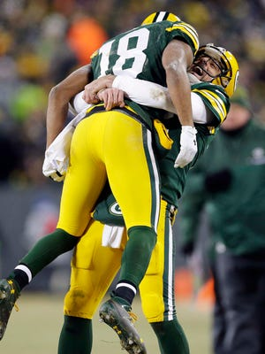 Green Bay Packers wide receiver Randall Cobb (18) celebrates with quarterback Aaron Rodgers (12) after scoring a touchdown on a hail mary in the 2nd quarter in the NFC Wild Card playoff football game at Lambeau Field.