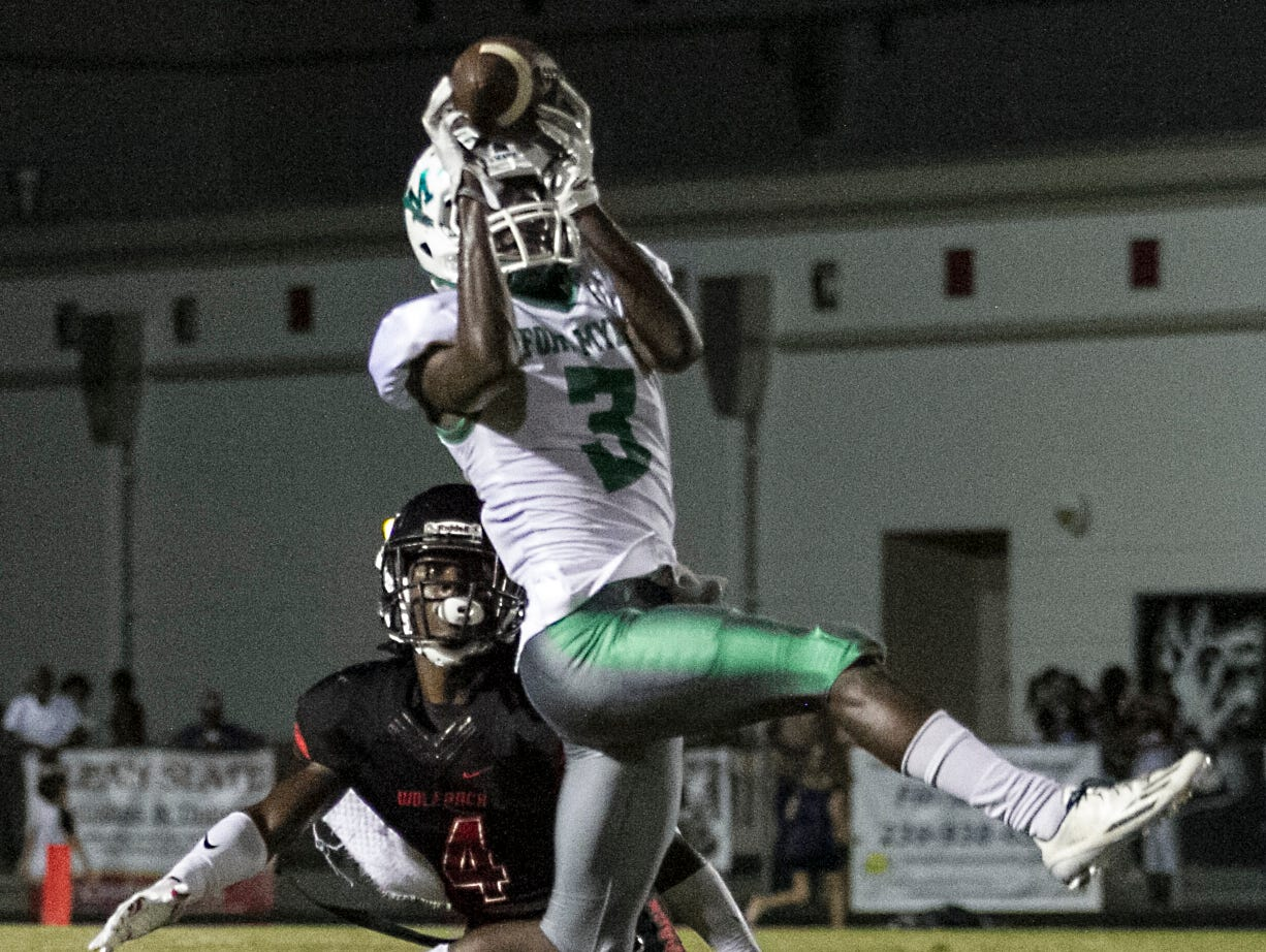 Fort Myers High School's Bensley Bornelus makes an acrobatic catchover Wolfpack defender Riley Ware IV Friday evening.