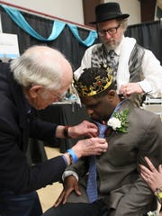 Scott Treggett (left) slips a tie aroundTony Partlow's neck and tightens it up as Jeff Joaquin adjusts his collar during the Night to Shine at the Kitsap Sun Pavilion on Friday, Feb. 9, 2018.