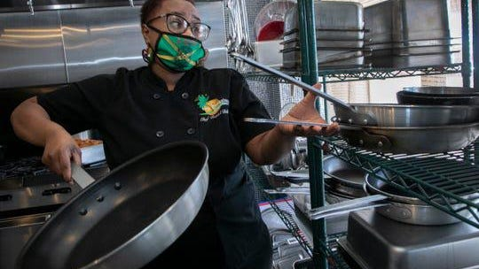 Flavors of Jamaica in Pontiac owner Reniel Billups, 39, reaches for cookware in the kitchen during a busy take out lunchtime Friday, July 24, 2020.