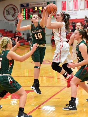 Bellevue's Jenna Strayer tries to get a shot off Tuesday as Oak Harbor's Logan Harris tries to block it.