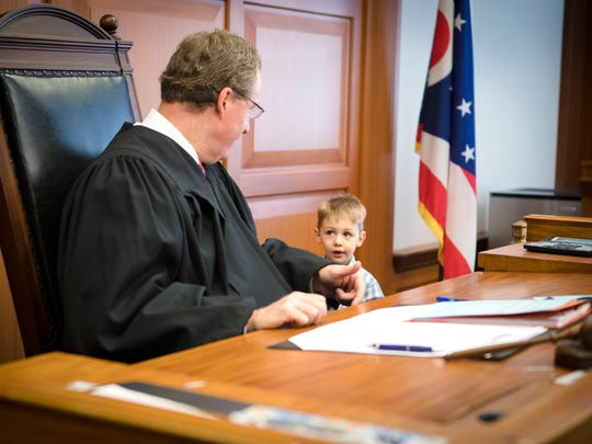 Thu., Jan. 25, 2018: Hamilton County Judge Ralph Winkler talks to Lucas, 2, during his adoption proceedings. Winkler said he always suggests that parents let their kids run, and so Lucas made laps around the courtroom. Cameron and Jennifer Knight have fostered several children over the last two years, and Lucas is their first adoption. The Enquirer/Carrie Cochran