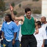 Golden State Warriors interim head coach Luke Walton poses for a photo with an inmate painting during the Warriors vs prisoners game at San Quentin. The painting was created by reusing old paint.