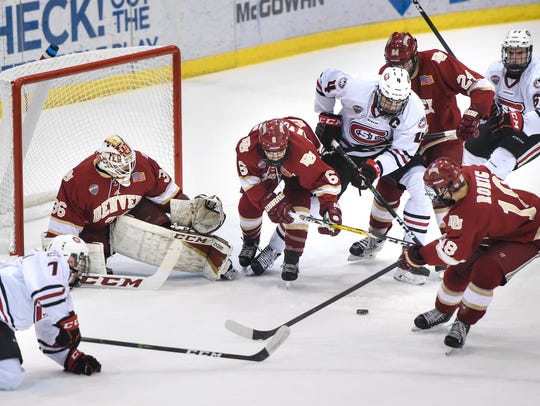 Players battle for control of the puck in front of