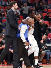 Pistons guard Reggie Jackson (1) is helped off the