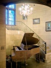 A piano sits at the bottom of a spiral staircase inside