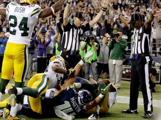 """In the infamous """"Fail Mary"""" game, official Lance Easley signals a touchdown by Seahawks wide receiver Golden Tate against the Packers on the last play of the game on Sept. 24, 2012, in Seattle. The NFL later acknowledged that offensive pass interference should have been called."""
