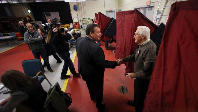 New Jersey Gov. Chris Christie shakes hands with poll worker James Banko before casting his ballot on Election Day at the Emergency Services Building on Tuesday in Mendham.