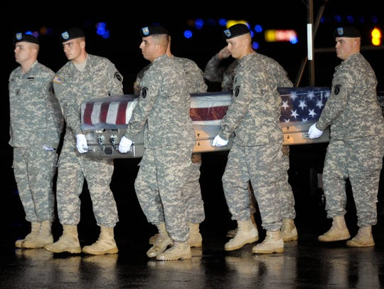 An Army carry team carries the transfer case containing