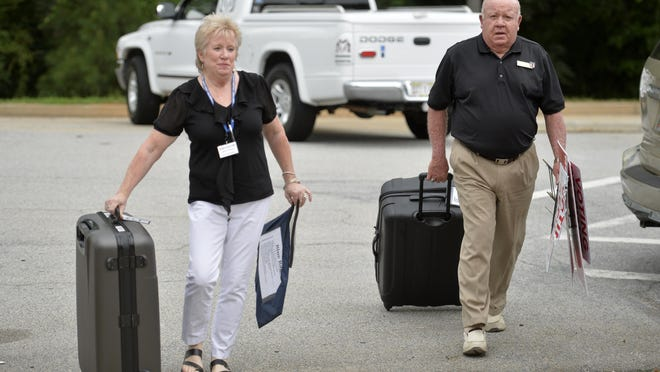 Election officials Lori Patterson and Rusty Wade roll cases containing voting results from a Columbia County precinct into the Government Complex in Evans, Ga., Tuesday evening July 24, 2018.