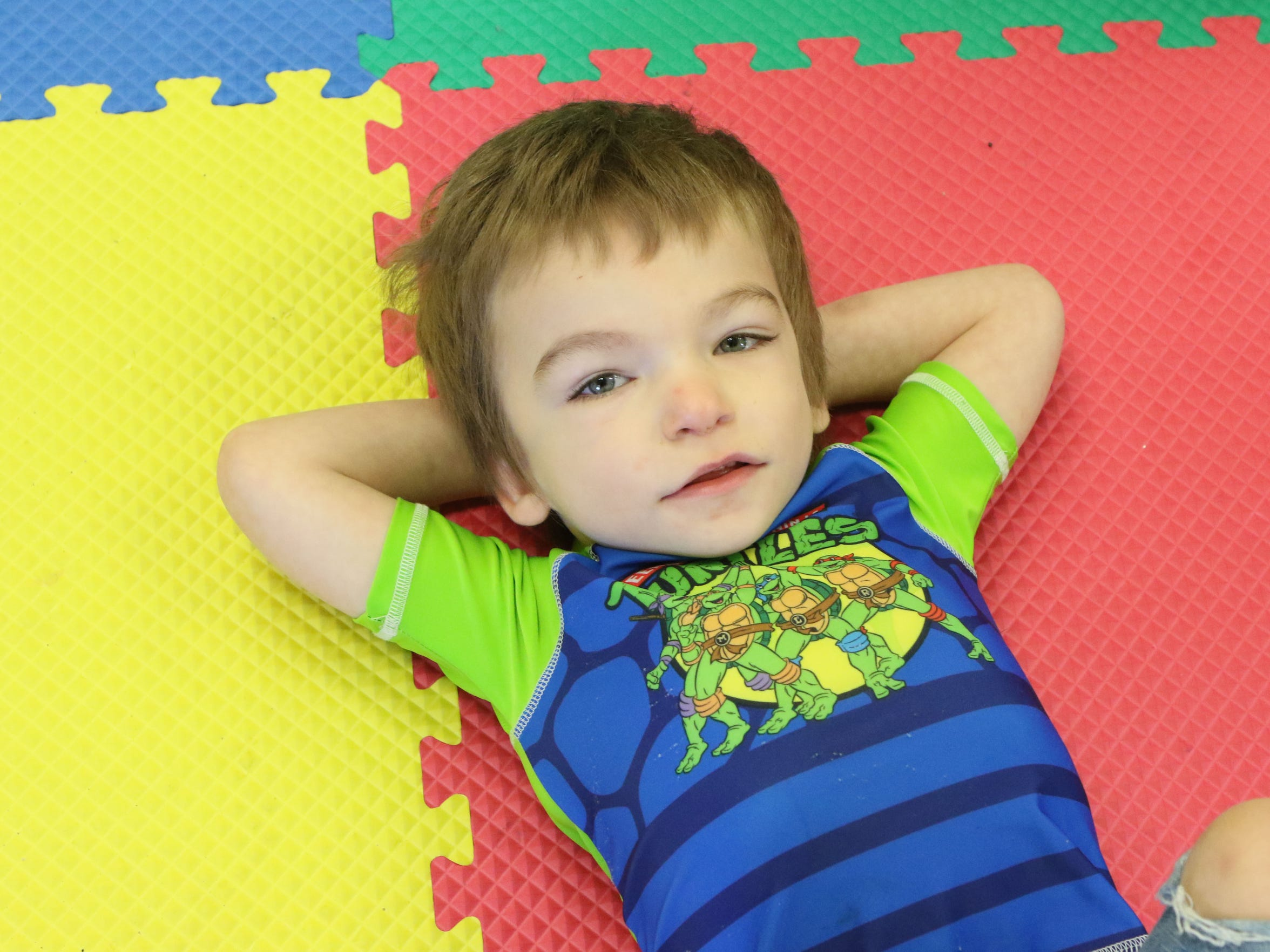 Collin Forest, 4, lies on the ground during playtime