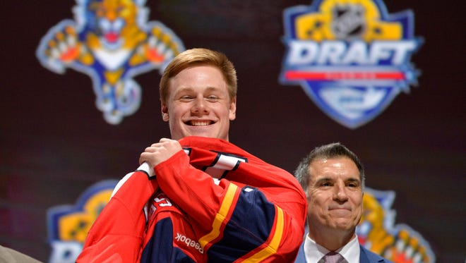 Jun 26, 2015: Lawson Crouse puts on a team jersey after being selected as the number eleven overall pick to the Florida Panthers in the first round of the 2015 NHL Draft at BB&T Center.