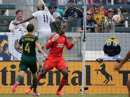Los Angeles Galaxy's Gyasi Zardes (11) scores against Portland Timbers goalkeeper Donovan Ricketts during the first half of an MLS soccer match on Saturday, Aug. 2, 2014, in Carson, Calif. (AP Photo/Jae C. Hong)