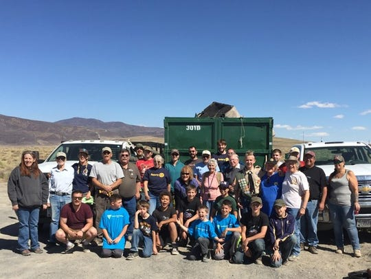 Volunteers stand in front of one of the filed dumpsters