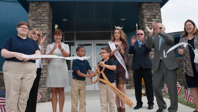 From left, student Rebecca Smiley, Executive Director/Greater Vineland Chamber of Commerce Dawn Hunter, school principal Deborah Morton, students Dominic Garcia and Satteed Maitland, Miss Cumberland County Sarah Pepitone, Esteban Garcia, Board of Trustees President Gary Stanker and Executive Director of Vineland Public Charter School Ann Garcia react after students cut the ribbon Friday at the new Vineland Public Charter School.