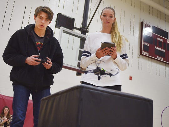O'Gorman high school student Joe Larson tries to land a  drone on a surface while Roosevelt High School Flight Club member Kim Weaver observes during the drone flying event Friday, Jan. 12, at the school in Sioux Falls. The Flight Club is for students interested in flying drones and the use of drones.
