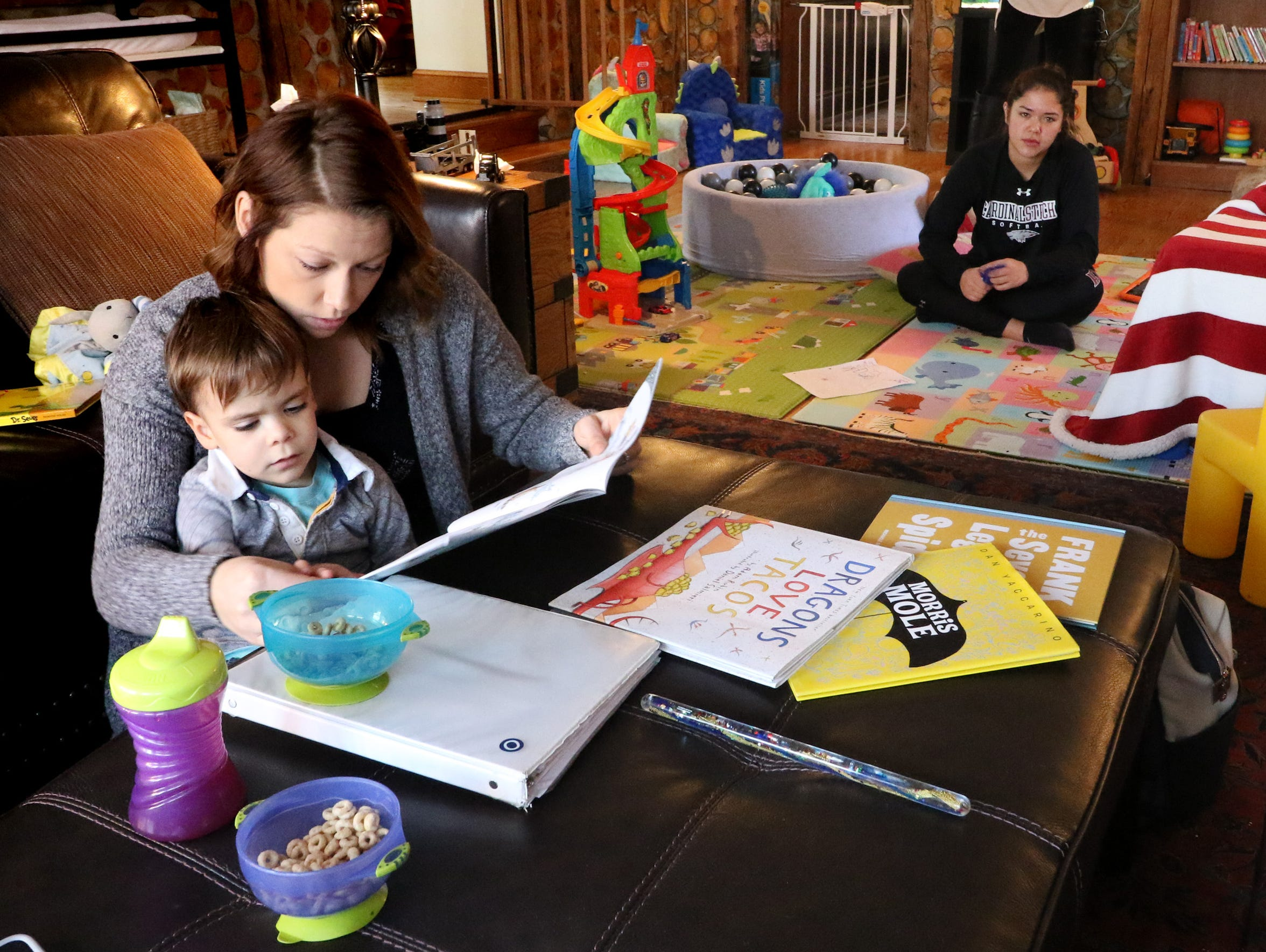 Sally Kubasa, a behavioral treatment therapist, reads to James Crimmins, 3, as part of his home therapy for his diagnosis of Autism to prepare him to attend school with his peers.