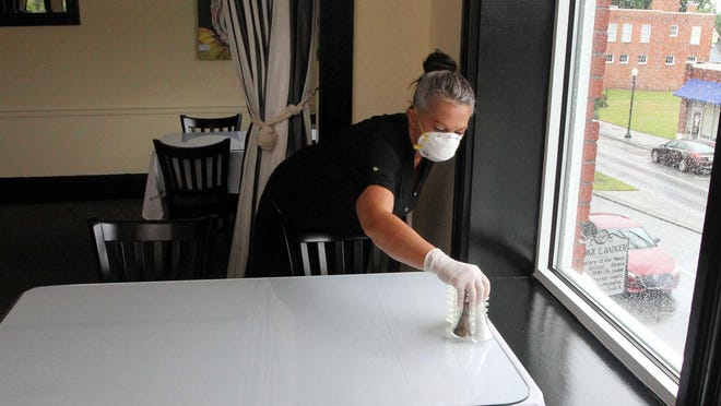 The Chelsea staff member Amy Daughety works to prepare the landmark restaurant for dining patrons before the May 22 reopening to dine-in customers.