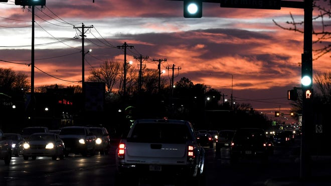 Motorists make their way along Kansas Avenue Wednesday as sunlight paints the clouds with hightlights near sunset.