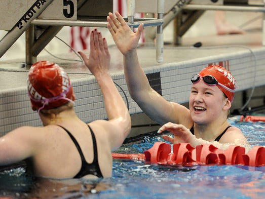 Fishers swimmer Lauryn Parrish, right, is congratulated by teammate Emily Moser after winning the 200 Yard Freestyle with a time of 1:49.02 during the IHSAA Girls Swimming Sectional, Saturday, February 8, 2014, at Fishers High School.