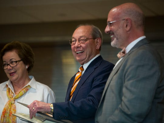 At center University of Tennessee Chancellor Jimmy Cheek smiles on stage with his wife Illeen and University of Tennessee President Joseph DiPietro as he is presented a gift in Neyland Stadium Wednesday, Feb. 8, 2017.