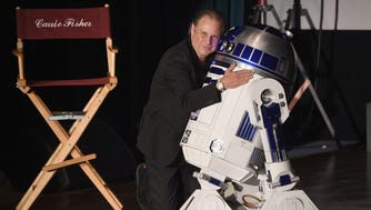 Todd Fisher comforts a mournful R2D2 at the memorial service for Carrie Fisher and Debbie Reynolds.
