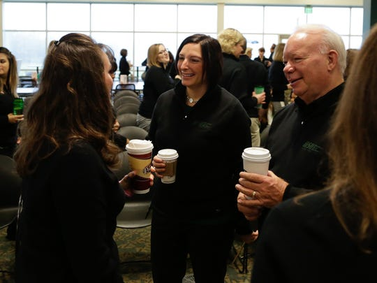 In Oct. 2014, MSUFCU future CEO April Clobes (center) and current CEO Patrick McPharlinin (right) chat with employees following a fun all employee meeting while celebrating National Credit Union Day at the headquarters in East Lansing before the start of the work day.